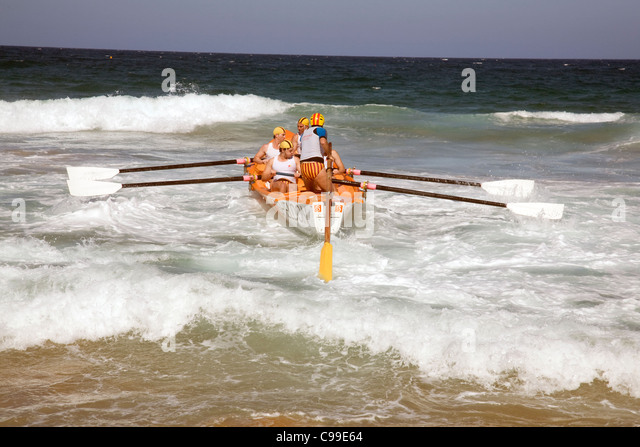 crew of a traditional australian lifeboat surf rescue boat rowing in a race off newport beach,sydney - Stock Image