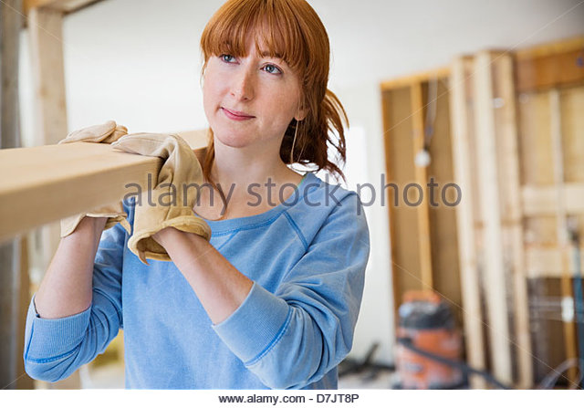Woman carrying lumber in home - Stock Image