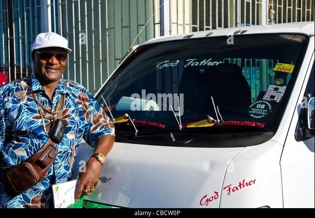 Smiling taxi driver with minivan, Roseau Dominica - Stock Image