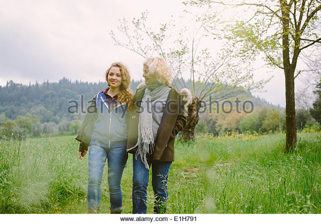 Mature woman and teenage daughter strolling in field - Stock-Bilder