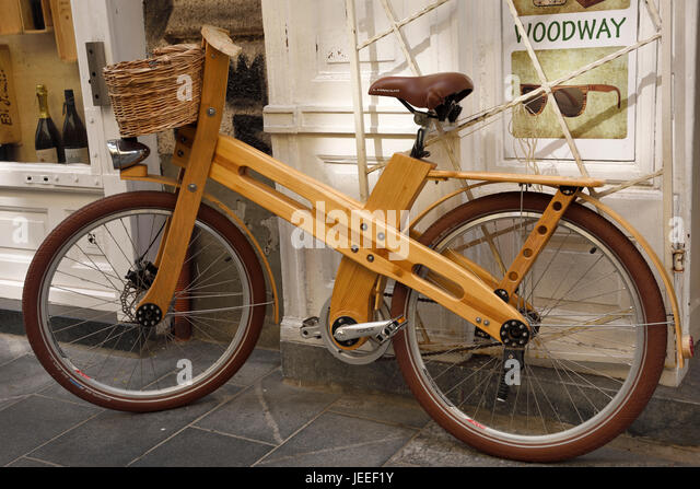 Environmentally friendly wood bicycle tied to a shop in the old town area of Ljubljana Slovenia - Stock Image