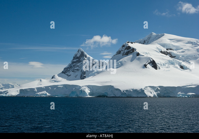 Small cloud forming against a clear blue sky on the peak of a snow covered mountain in the Antarctic peninsula - Stock Image