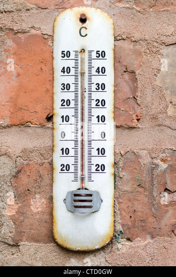 Old rusty thermometer hung outdoors on a red brick wall - Stock Image