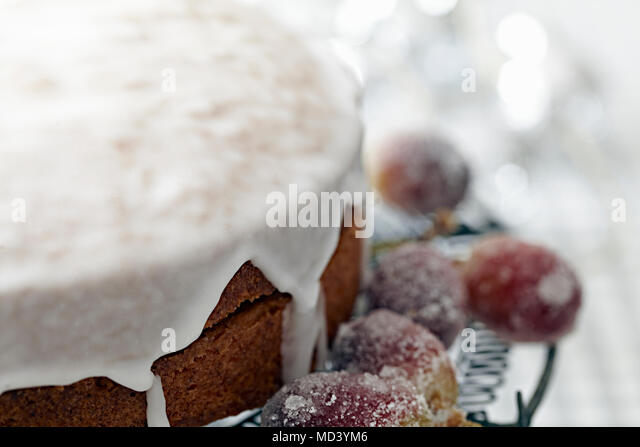 Iced cake on cake stand with sugar frosted grapes, close up - Stock Image