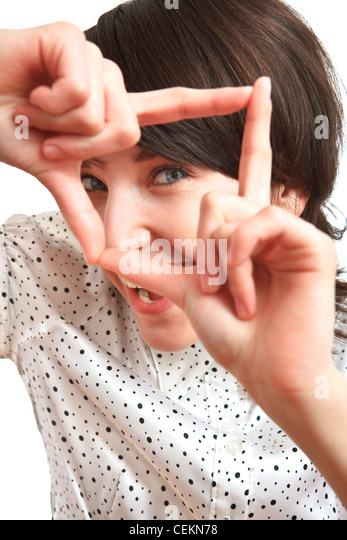 girl smiling and taking a virtual photo with her hands - Stock Image