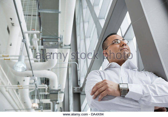 Low angle view of businessman standing in office building - Stock Image