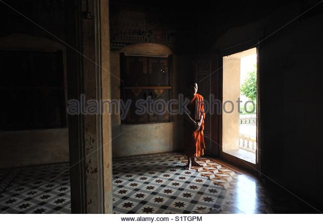Buddhist monk standing near the entrance to a Temple in Cambodia, Asia - Stock Image