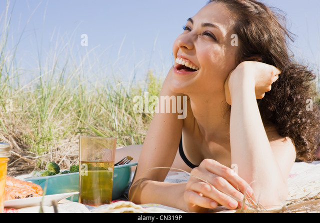 Woman laughing on picnic blanket - Stock Image