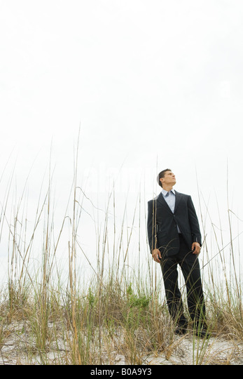 Businessman standing in tall grass, looking up, full length - Stock Image