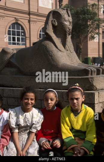 Egypt Cairo Egyptian Museum female Muslim students heads covered sphinx statue - Stock Image