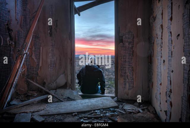 USA, Idaho, Rear view of man sitting on doorstep and looking at sunset - Stock-Bilder