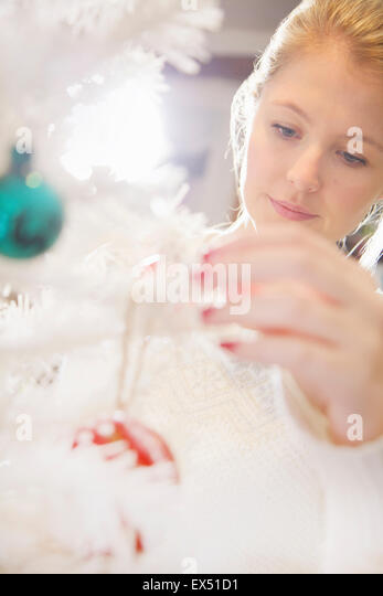 Close up of Young Woman Decorating Christmas Tree - Stock Image