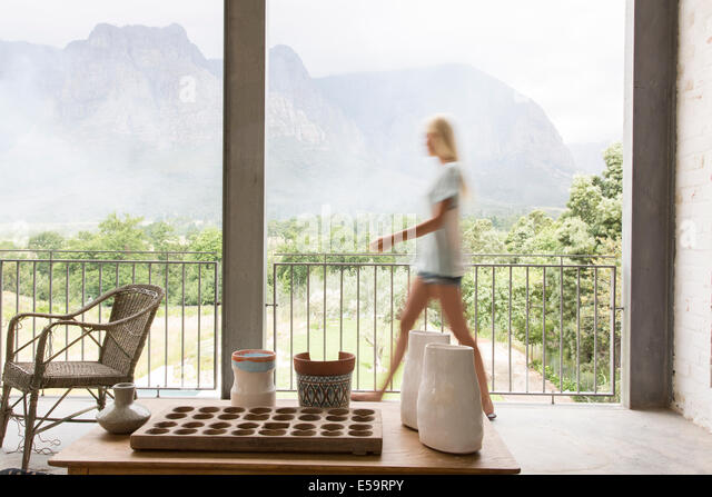 Blurred view of woman walking on patio - Stock Image
