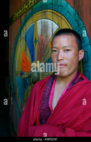 Portrait of a young monk in front of the Tongsa Dzong entrance, Bhutan - Stock Image