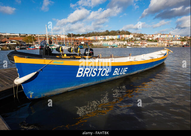 Bristol Pilot Gig 'Bristol Blue' rowing boat berthed in the floating harbour with colourful houses of Cliftonwood - Stock Image
