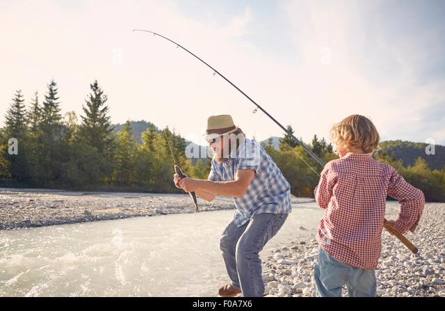 Mid adult man and boy next to river using fishing rod to catch fish - Stock Image