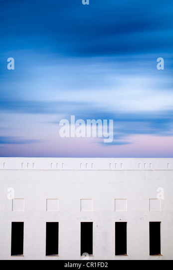 Moving clouds over a building. Long exposure shot. - Stock Image