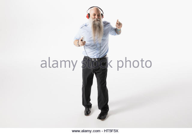 Cool hipster businessman with beard dancing, listening to music with headphones against white background - Stock-Bilder
