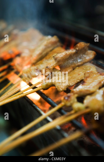 Pork skewers on barbecue grill - Stock Image