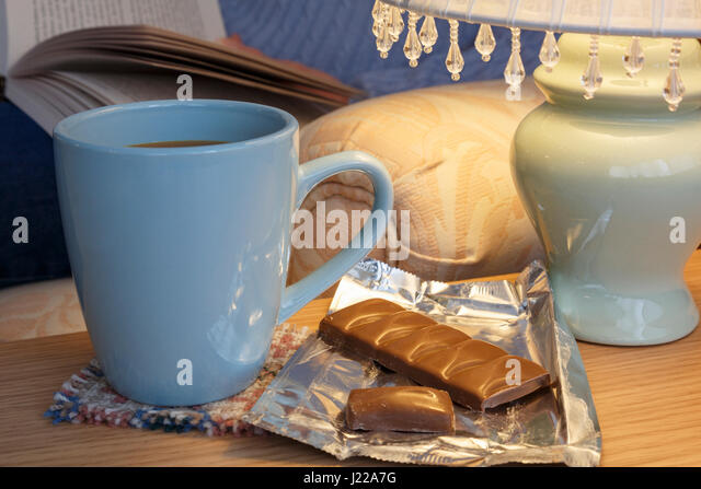 Everyday homely hygge scene of a person relaxing reading a book with a mug of coffee and bar of chocolate by a table - Stock-Bilder