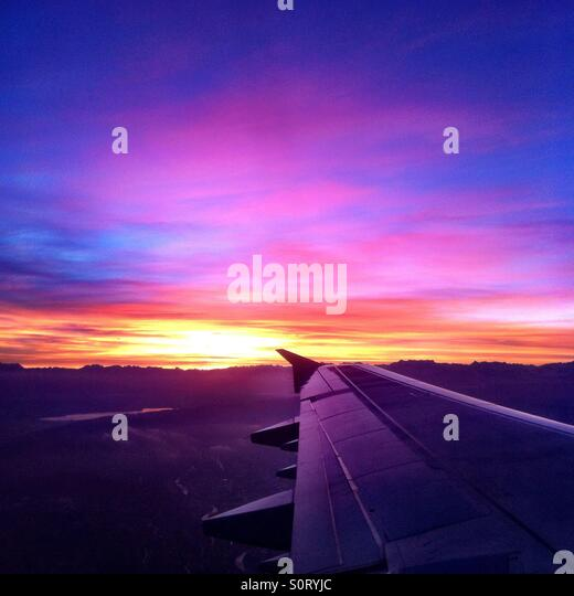 Beautiful sunrise at take off from Zurich, Switzerland, showing wing and mountains. - Stock Image