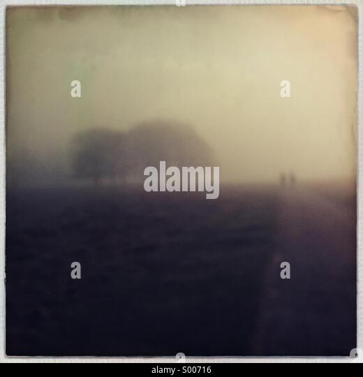 Couple Walking On A Misty Road - Stock-Bilder