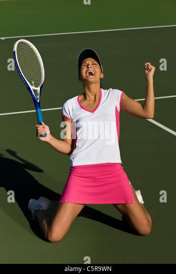 Tennis player celebrates winning match. - Stock Image