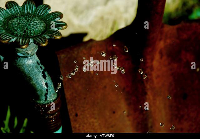 Springs a Leak - Copper Faucet, Hose, & Rusty Shovel - Stock Image
