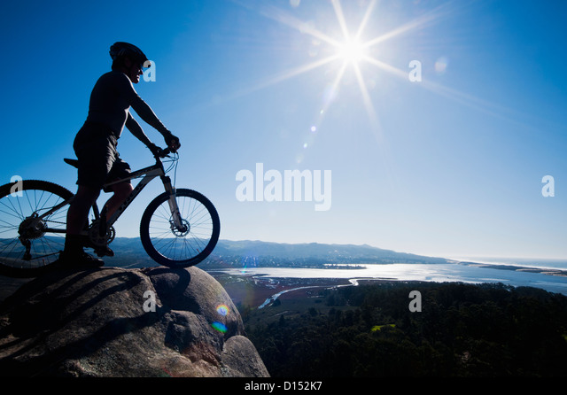 California, Morro Bay State Park, Man On Bicycle Looks Over Morro Bay From Cliff. - Stock Image