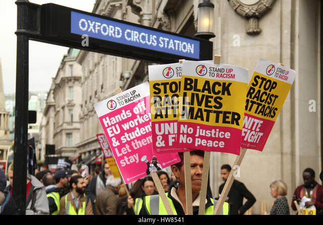 London, UK. March 18, 2017: A campaigner holds placards by Oxford Circus station ahead of the Stand Up To Racism - Stock Image