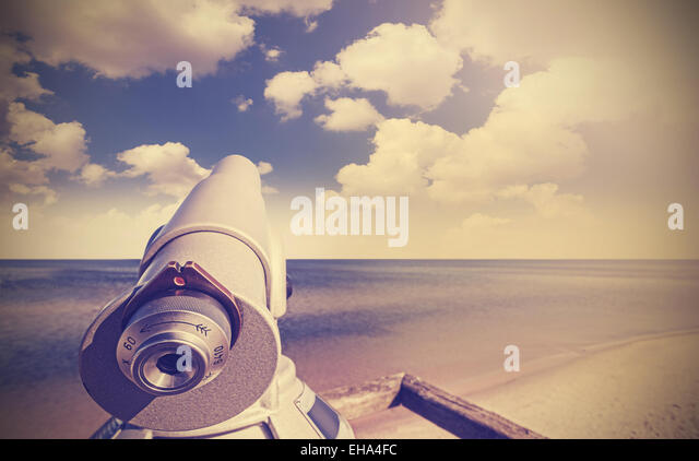 Retro toned picture of telescope on a beach pointed at beautiful sky. - Stock-Bilder