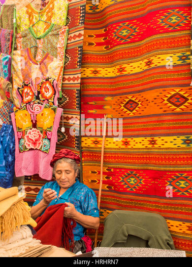 Woman sewing in market with background of handmade rugs, Oaxaca, Mexico, North America - Stock-Bilder