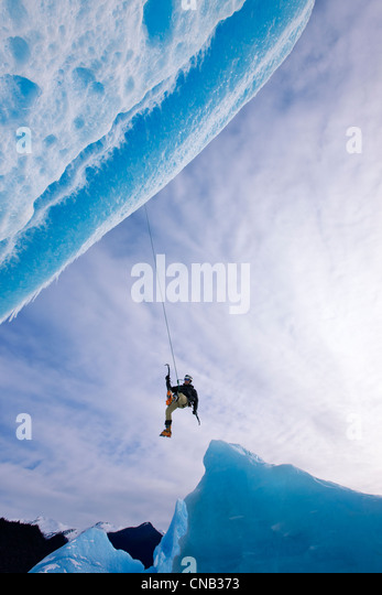 An ice climber swings down from rope to reach face of a large iceberg frozen into Mendenhall Lake, Juneau, Alaska, - Stock-Bilder