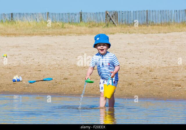 Portrait of small boy collecting seawater in toy bucket at beach, Marennes, Charente-Maritime, France - Stock Image