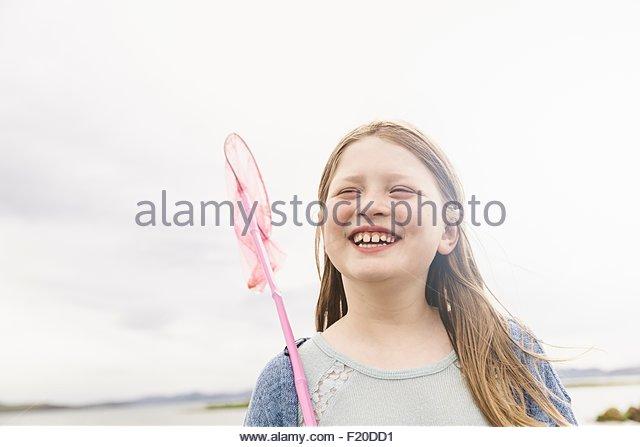 Girl with fishing net at lakeside, Thingvellir, Iceland - Stock Image