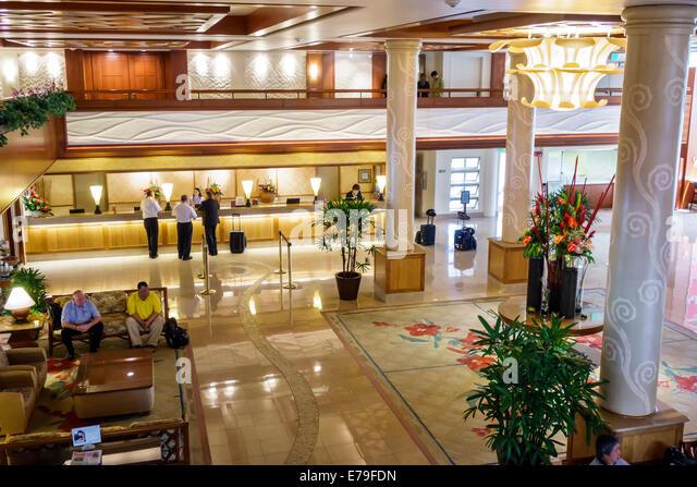 Waikiki Beach Honolulu Hawaii Hawaiian Oahu Hilton hotel lobby front desk reservations guests - Stock Image