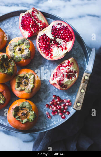 Fuyu Persimmons and pomegranate fruits - Stock Image