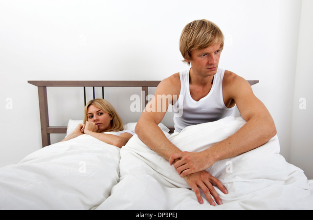 Angry man sitting on bed with woman in house - Stock Image