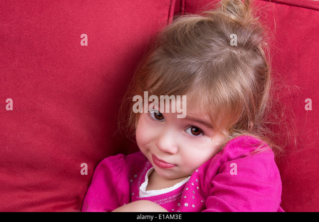 Shy little girl looking at the camera with big eyes as she snuggles down in a comfortable couch - Stock Image