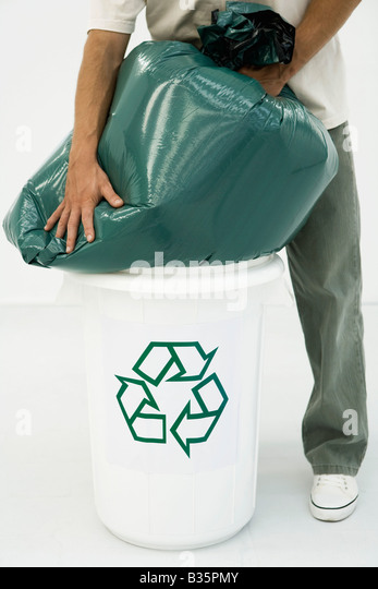 Man forcing large garbage bag into recycling bin, cropped view - Stock Image