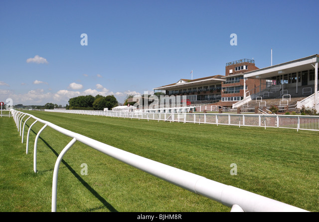 Folkestone, Kent, UK. Horse racing racecourse finishing straight and grandstand - Stock Image