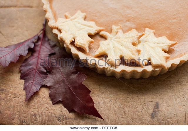 Maple leaf cookies on pumpkin pie - Stock Image