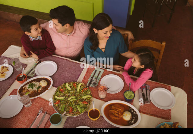 High angle view of Hispanic parents and children in restaurant - Stock Image
