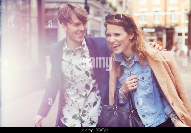 Stylish couple laughing on street, London, UK - Stock Image