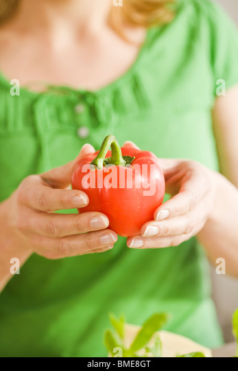 Woman holding a pepper, Sweden. - Stock Image