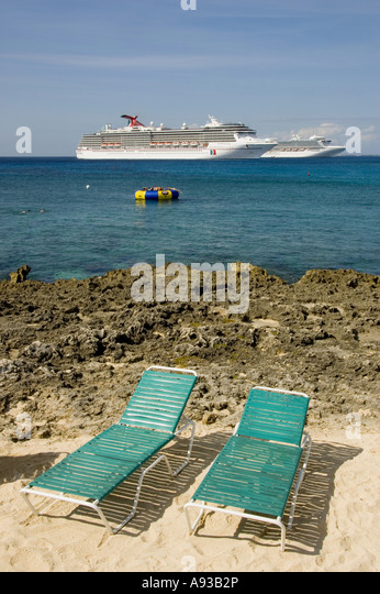 Grand Cayman George Town  cruise ships  two empty beach lounge chairs - Stock Image