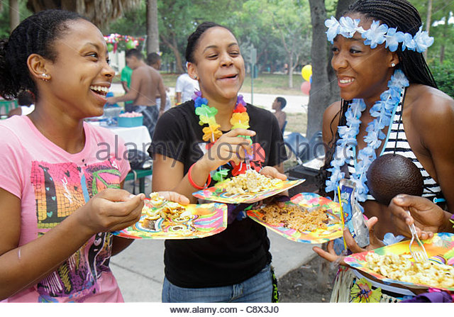 Miami Beach Florida North Beach North Shore Park luau party Black girl teen lei plate eating - Stock Image