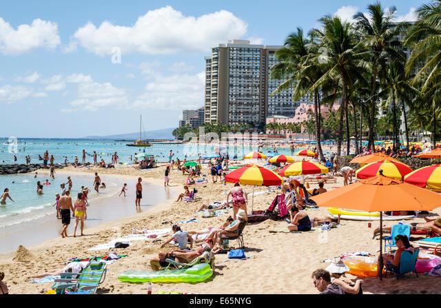 Hawaii Hawaiian Honolulu Waikiki Beach resort Kuhio Beach State Park Pacific Ocean sunbathers umbrellas families - Stock Image