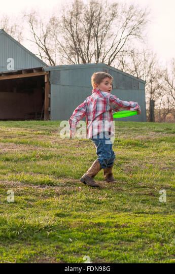 Boy wearing boots throwing frisbee on farm - Stock Image