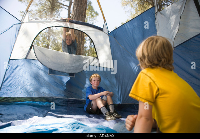 Two young boys sitting in an empty tent - Stock-Bilder